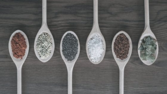 Dried spices on wooden serving spoons