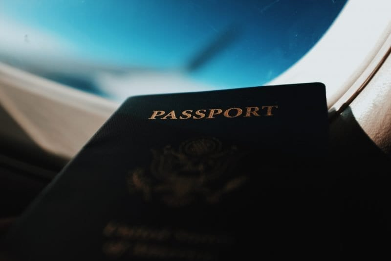 silhouette of passport booklet with airplane window background