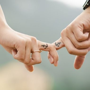 Couple's fingers with anchor tattoos - strengthen your love