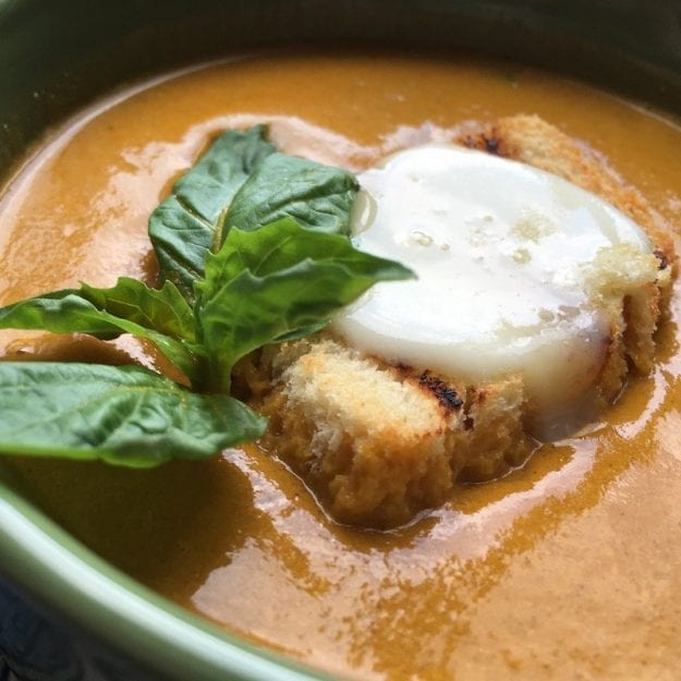 Slow Roasted Tomato Soup in green bowl with Grilled Cheese Crouton and basil garnish - healthy soups