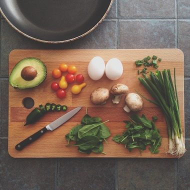 Wooden cutting board on tiled counter covered with assortment of healthy foods