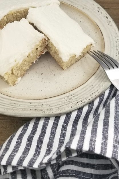 Whiskey Cream Cheese Frosted Banana Bars on a beige plate with striped napkin