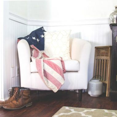 Boots on the floor next to a white chair draped with an American flag