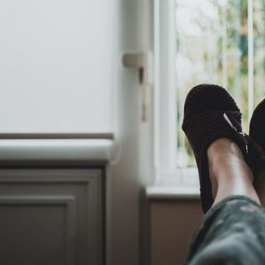 Person kicking up their feet in black fuzzy slippers to relax during the pandemic