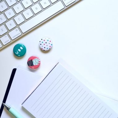 Photo Round Buttons and note pad on white desktop are items that will get your home organized