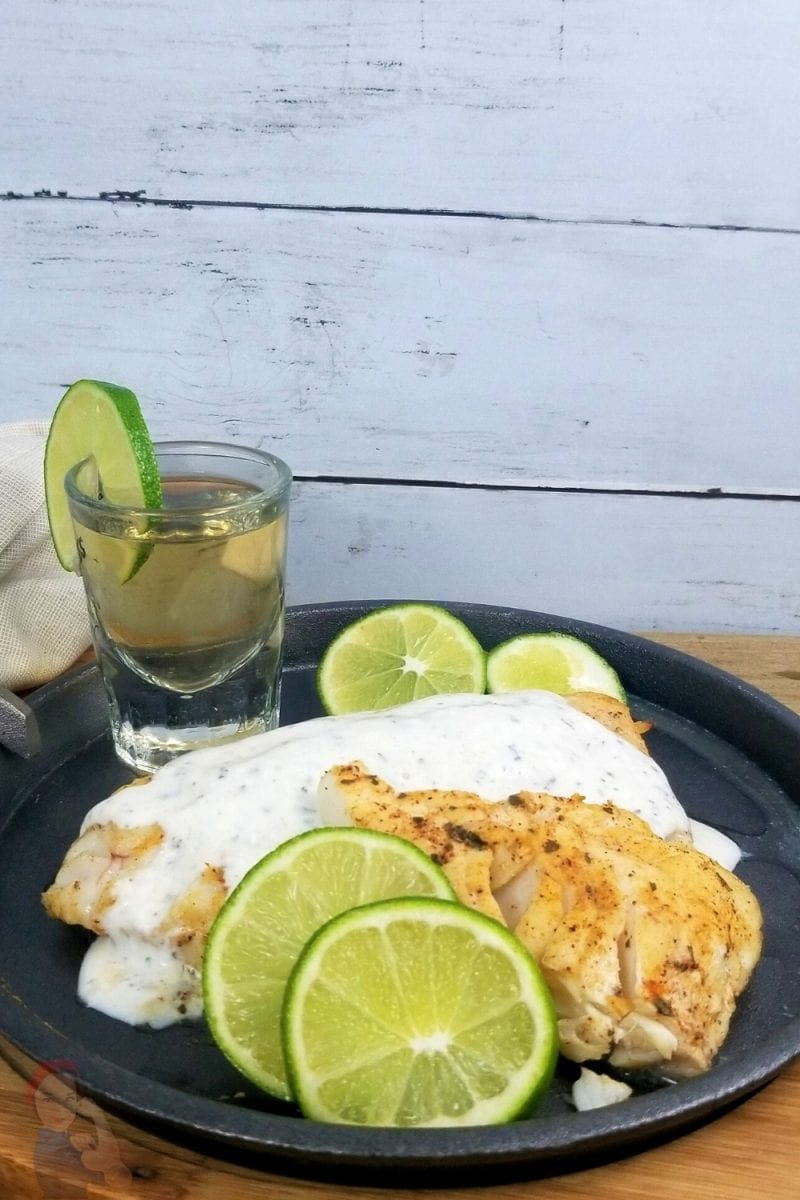 Grilled Tequila Lime Cod with a Cilantro Lime Drizzle on a cast iron plate accented with lime slices and a shot of tequila.