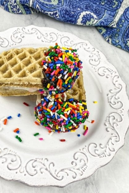 Rainbow Sprinkles cover chocolate ends of waffle ice cream sandwiches on a white plate