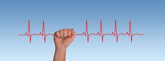 Hand holding onto a heartbeat line showing a normal rhythm unlike when you experience anxiety at the doctor
