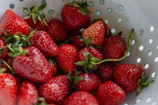 Pre-washed strawberries in a colander to make them quick to grab so we'll eat more strawberries!