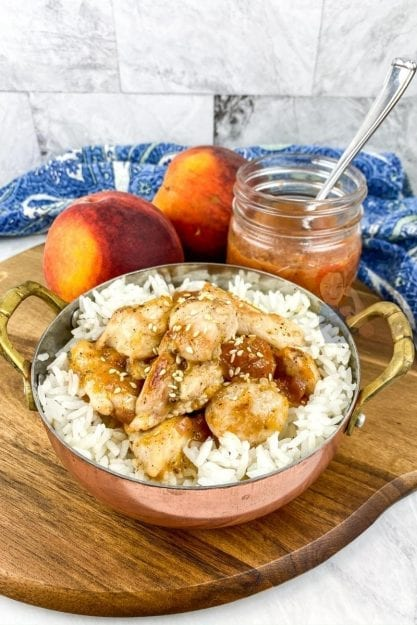 A bowl full of chicken and rice with warm peach compote is a sweet and savory dish that the entire family will love!