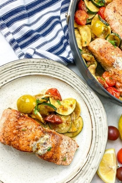 Crisp salmon with summer squash, cherry tomatoes, and zucchini on a dinner plate