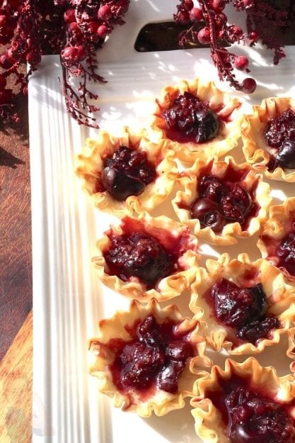 Brie and Dark Cherry Phyllo Bites on white serving tray