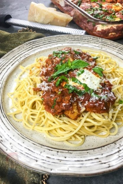 Plate of Chicken Parmesan with Spaghetti, Marinara Sauce, fresh herbs and cheese