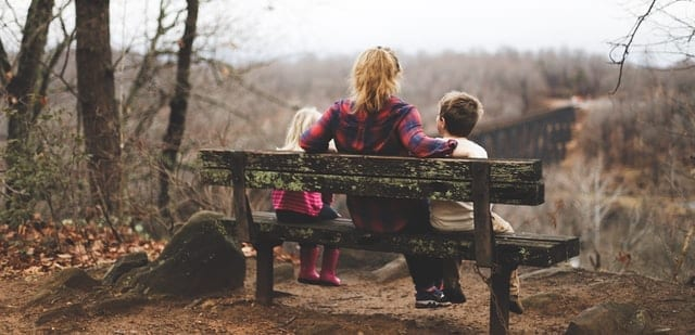 Woman sitting on a bench with her kids