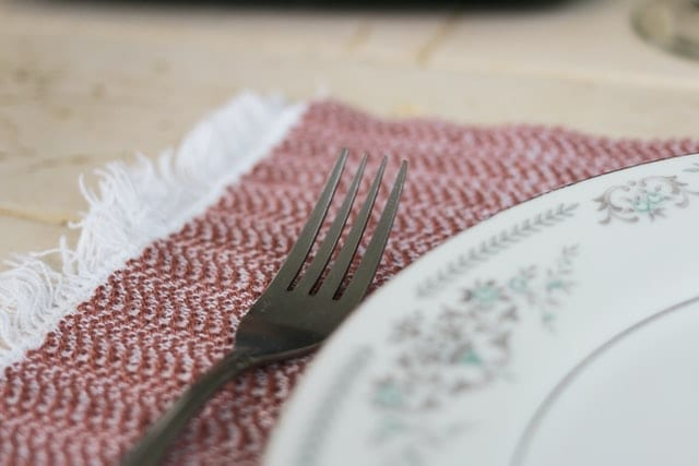 Dinner plate and fork on red and white placemat waiting on comfort food