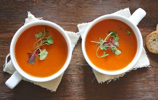 Tomato soup in soup bowls on wood table are one of many healthy meals to heal the body and soul this winter