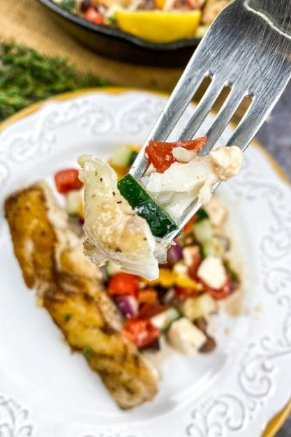 Fork holding a bite of Mediterranean Grouper with Tomato-Cucumber Salad