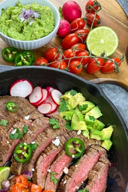 Carne Asada in cast iron skillet with guacamole, cherry tomatoes, limes, and jalapeños on a cutting board