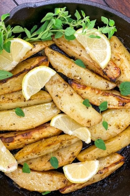 Crispy browned potato wedges in cast iron pan