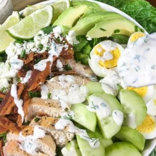 Spoon drizzling homemade ranch dressing on the Cobb Salad