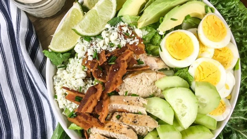 Top view of a Keto Cobb Salad - includes salad mix, bacon, eggs, avocados, and cheese crumbles