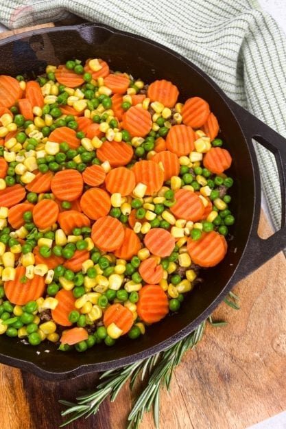 Vegetables layered on top of ground beef in a cast iron skillet prior to adding mashed potatoes on top to create Shepherd's Pie