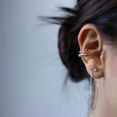 Woman's ears with silver earrings listening and unprotected from hearing stress