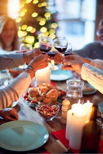 Family and friends dining at home celebrating with a pre-order a Thanksgiving meal of traditional food and decoration, all sitting on the table together making a toast