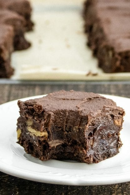 Fudgy Chocolate Walnut Brownie on a white plate with a bite taken out of it and brownies in the background