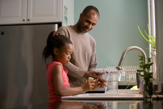 Father teaching daughter how to properly wash her hands to show how a family can be healthier