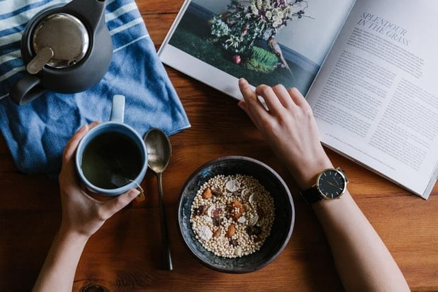 Person holding a blue ceramic mug of coffee with a bowl of breakfast, reading to increase healthy habits for the new year