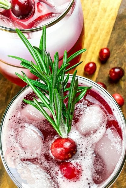 Cranberry and fresh rosemary garnish in a glass of the spritzer adds a festive touch to the drinks