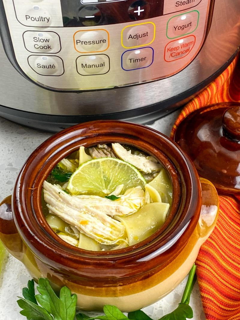 Bowl of IP soup in crock with lime on top beside IP