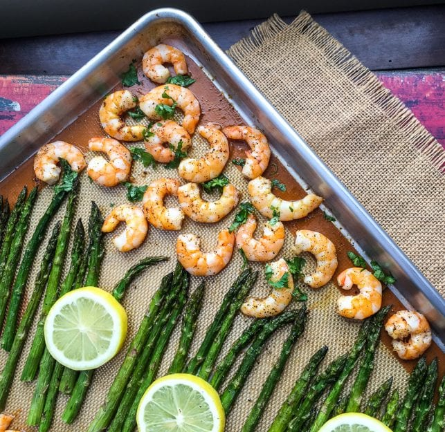 Half sheet baking pan lined with Silpat mat with asparagus, lemon slices, and seasoned shrimp on it