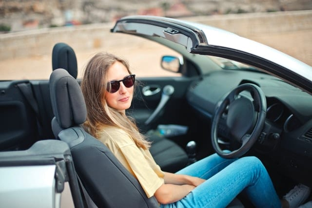 Girl sitting in a convertible - her parents are teaching a teen to drive