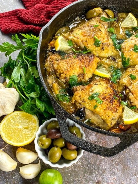 Cast Iron Chicken Provencal in pan with lemons, parsley, garlic and olives