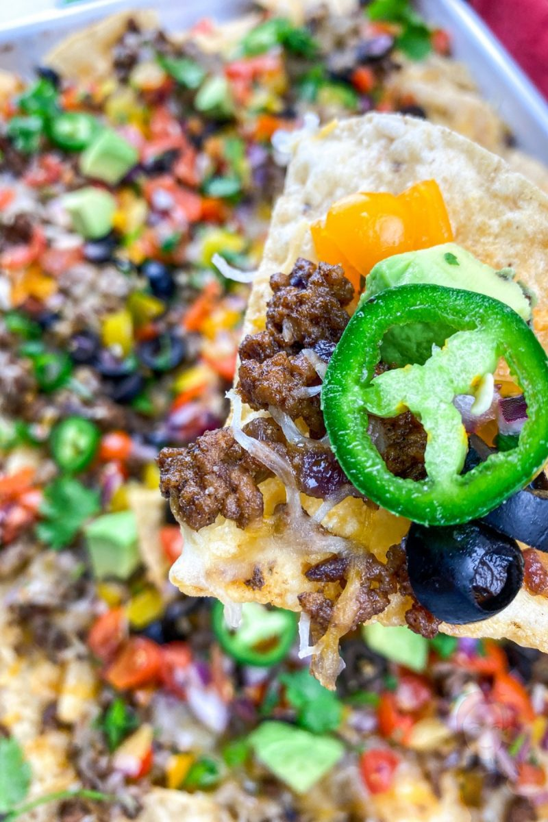 Up close view of a nacho chip holding the toppings of the loaded sheet pan nachos