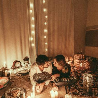 couple lying in the carpet with candlelight and pizza for the ideal Valentine's Day menu
