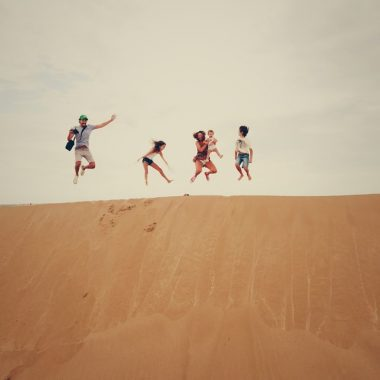 Family jumping in the air on top of a big hill after seeking more adventure