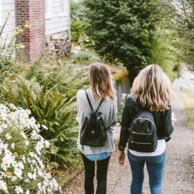 Two teen girls walking near a house with backpacks - there are several common mental health conditions for teens that we need to look out for!