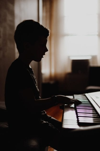 Child playing the piano after online music lessons
