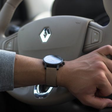 Hand with a watch holding a steering wheel of a car after performing 5 pre-driving checks