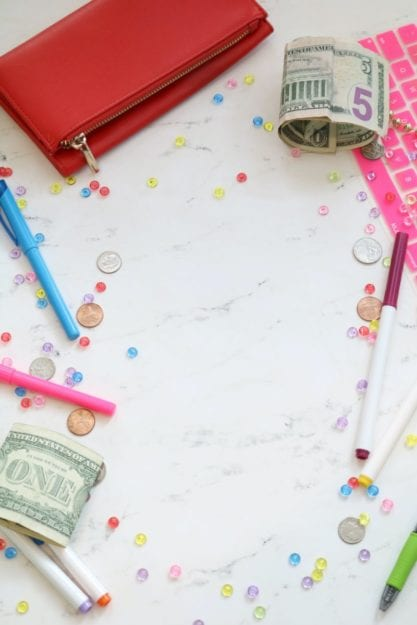 Marble money family finances stock photo and money styled stock photo for personal finance bloggers, business coaches, and entrepreneurs with a pink keyboard, colorful pens, cash, a red wallet, and more.