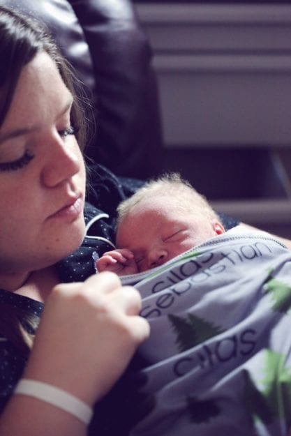 New mother holding her premature infant born at 34 weeks gestation during her postpartum period
