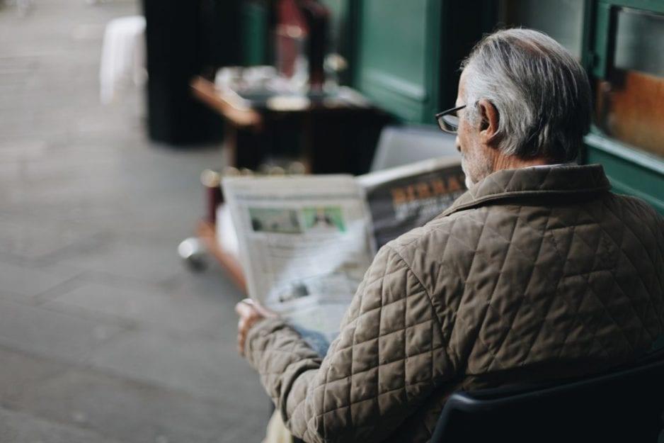 Man reading a newspaper about how hearing loss affects older adults