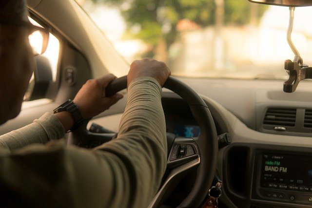 Hands on a steering wheels as a driver