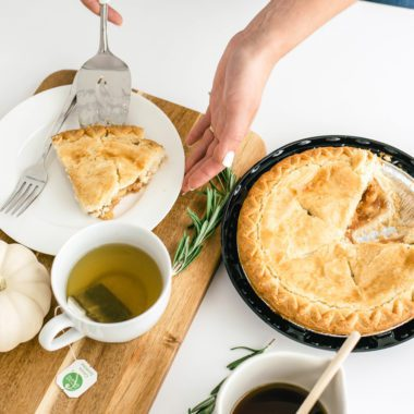 Homemade pie on a table with a piece being served. Cup of green tea. symbolizing frugal meal ideas